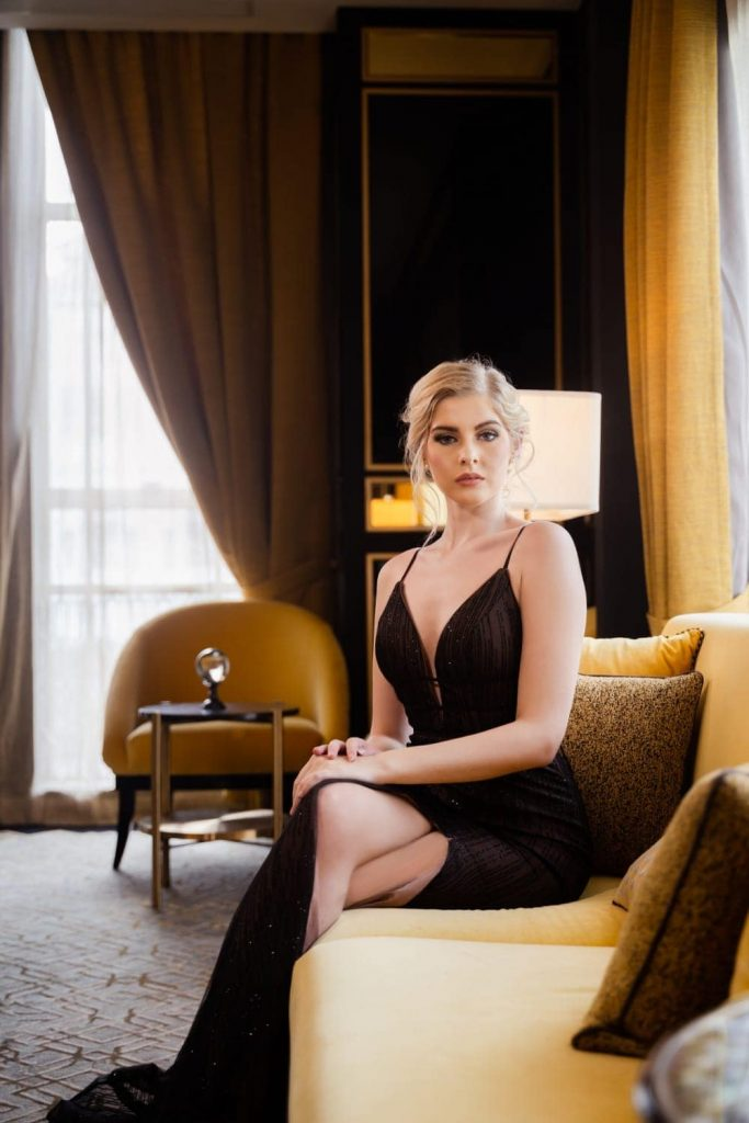 portrait photography singapore a woman in a black dress sitting on a sofa