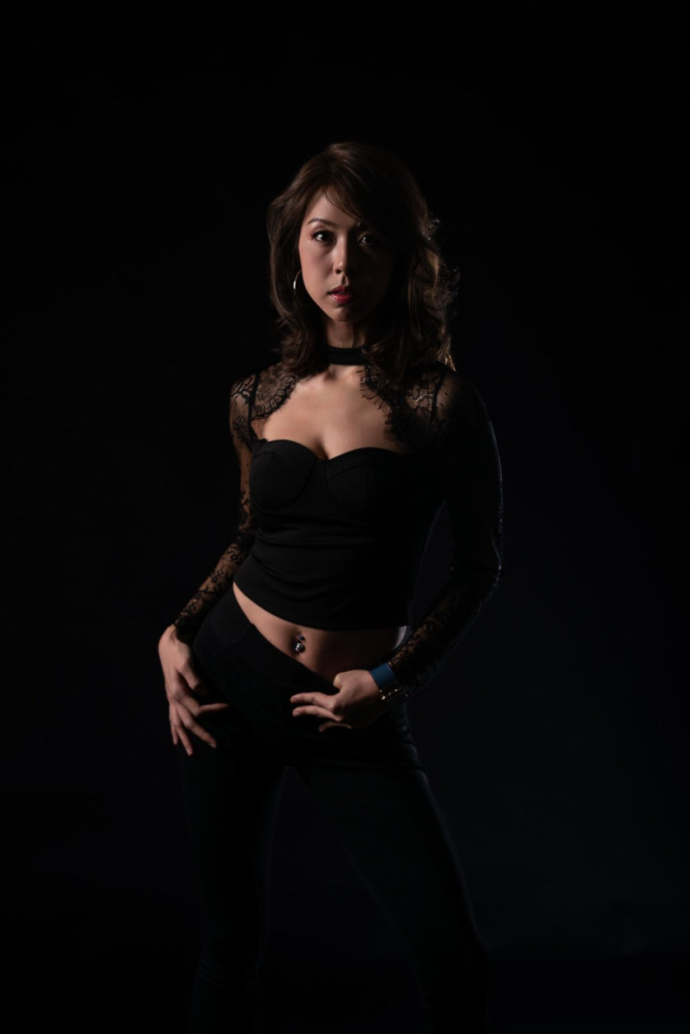 corporate headshot singapore a woman wearing a black top and jeans in a black-themed room