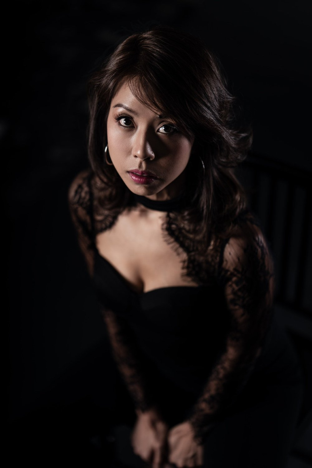 portrait photography singapore a woman posing for the photo in a dark-themed room