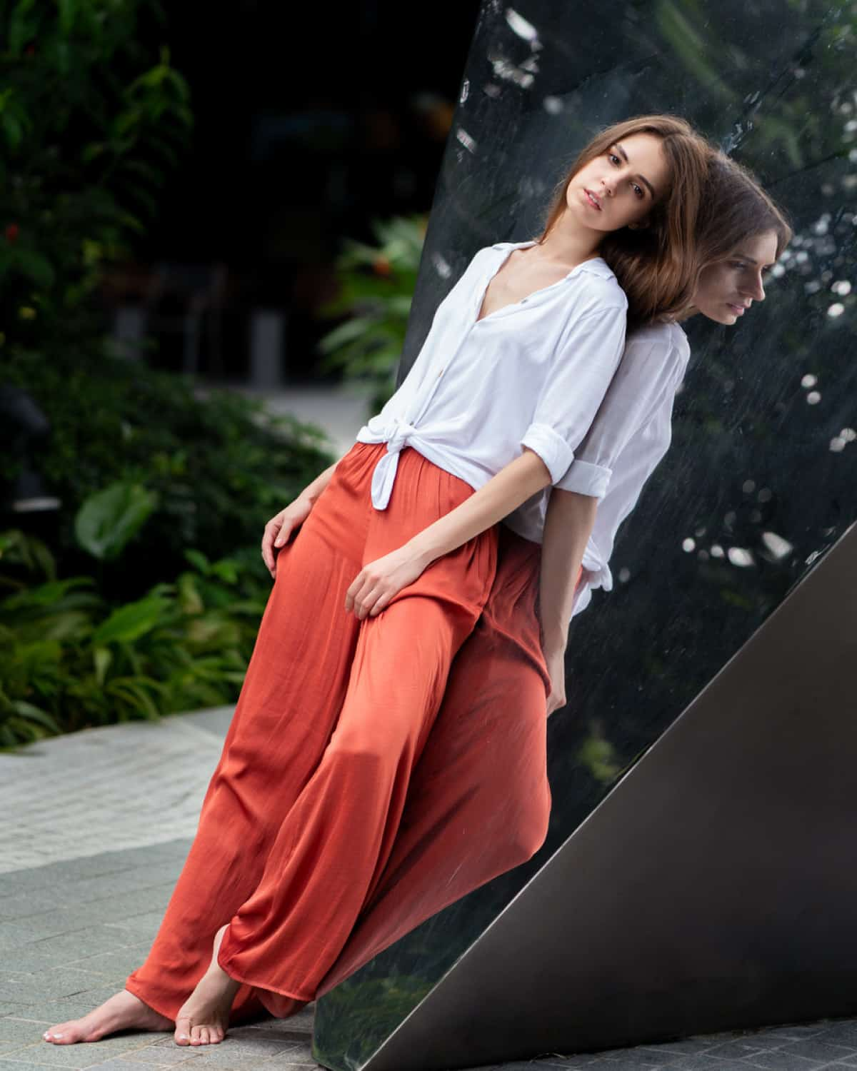 portrait photography singapore the woman is leaning on a reflective wall