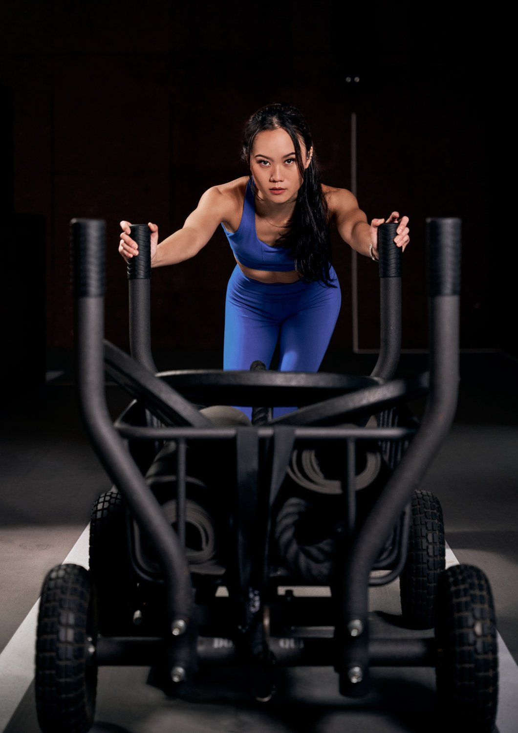 portrait photographers singapore an atheletic woman pushing a workout equipment