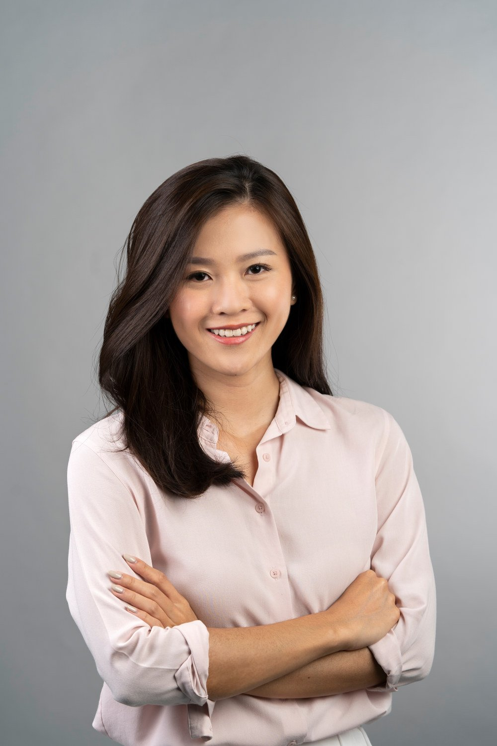 corporate headshot singapore a woman in light pink full-sleeved shirt