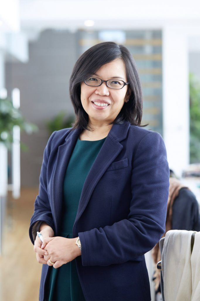 corporate photoshoot singapore a woman in a formal attire is smiling for the photo
