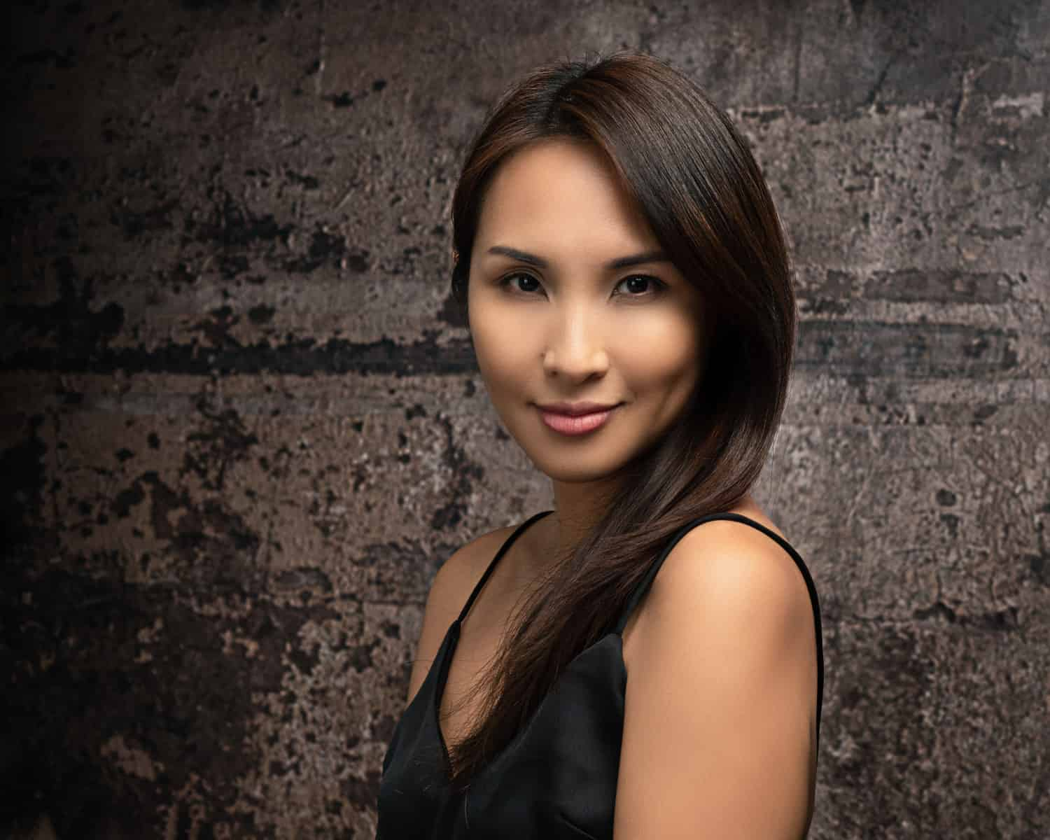 portrait photographer singapore a woman in a black top infront of a brick wall