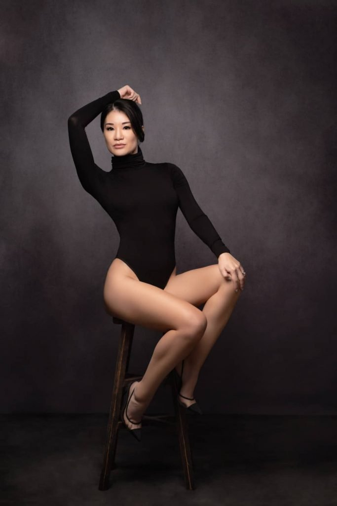 portrait photographer singapore a woman in a bodysuit and sitting on a stool
