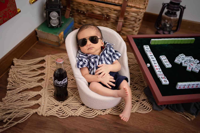 newborn photoshoot singapore baby is sleeping in a small bath tub beside a coke bottle