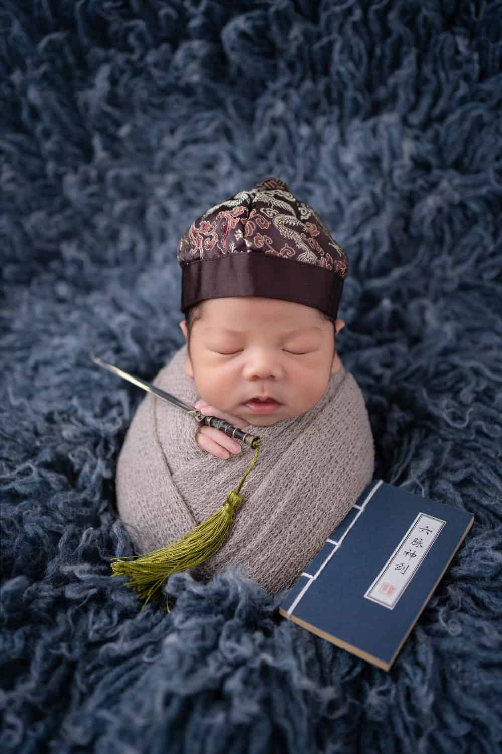 baby photoshoot singapore newborn wrapped in a comfortable blanket is wearing a traditional hat and has a chinese book.
