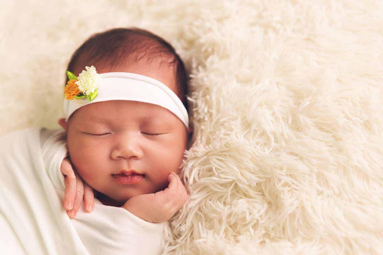 photoshoots for babies singapore a closer shot of sleeping newborn wearing a floral headband