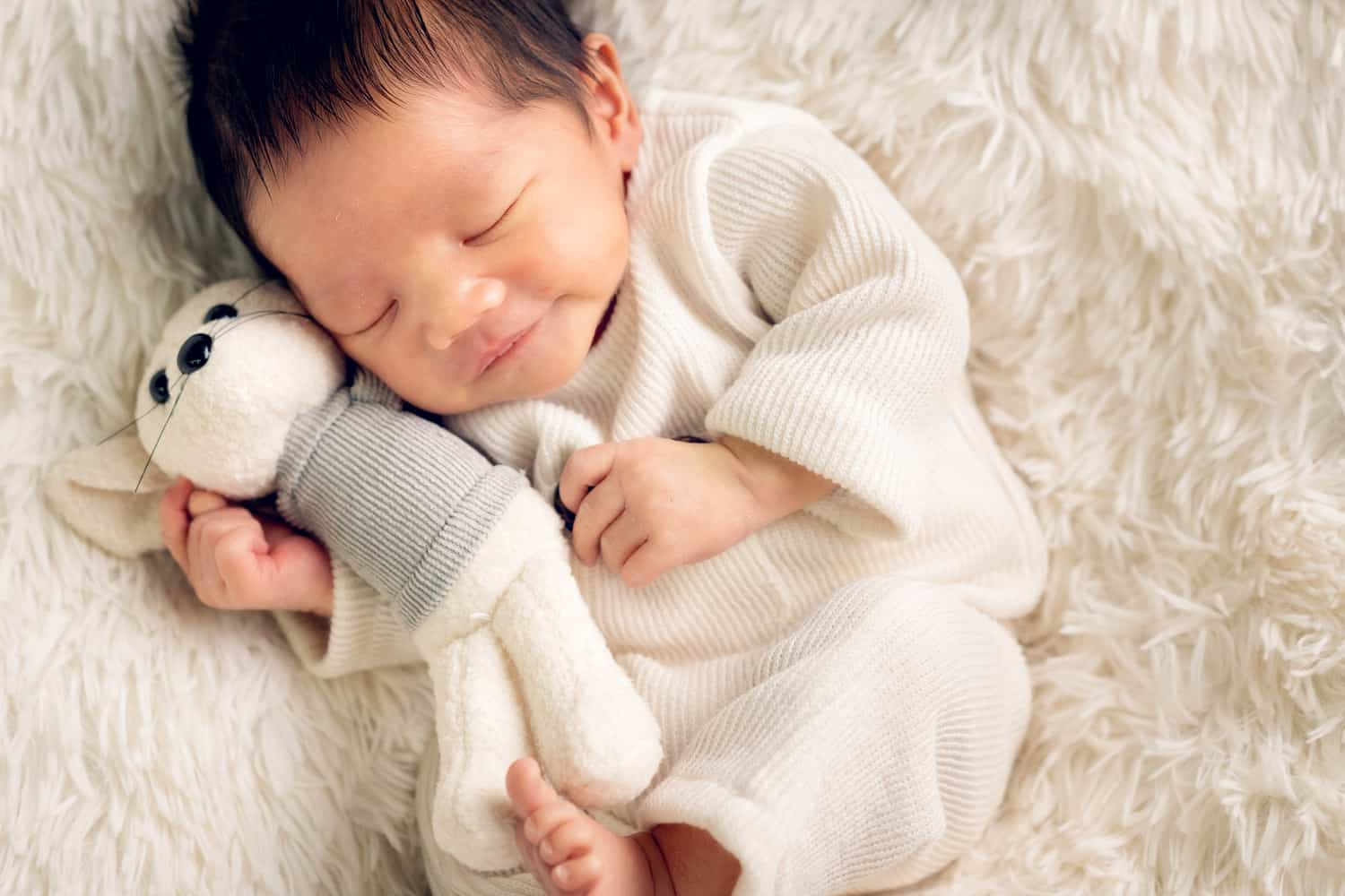 baby photoshoot singapore newborn sleeping with a white mouse toy